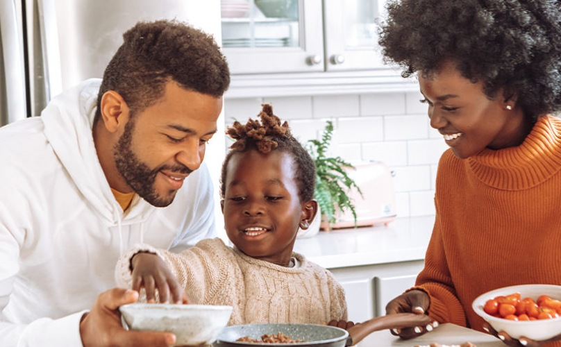 Family cooking dinner together in a well lit modern style kitchen