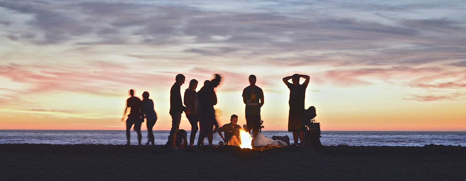A group of friends hanging out on the beach at sunset